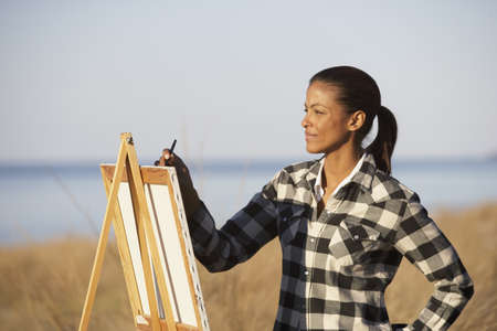 seriousness skill: African woman painting at an easel outdoors, Eastville, Virginia, United States