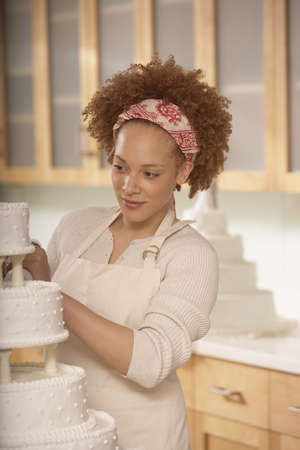 cake tier: African female baker decorating a wedding cake, Richmond, Virginia, United States LANG_EVOIMAGES