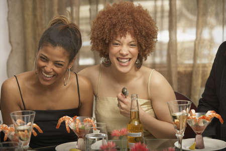 south western european descent: Two young African women laughing at a dinner party, Richmond, Virginia, United States LANG_EVOIMAGES