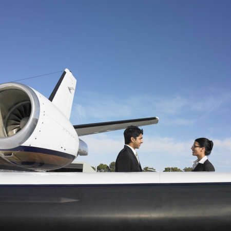 ostentatious: Businessman and businesswoman next to airplane, Perth, Australia