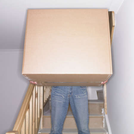 man carrying box: Man carrying box down stairs in new house