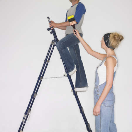 lower section view: Woman handing paintbrush to man on ladder LANG_EVOIMAGES