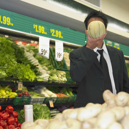 Businessman holding melon in front of his face in supermarket, Perth, Australia