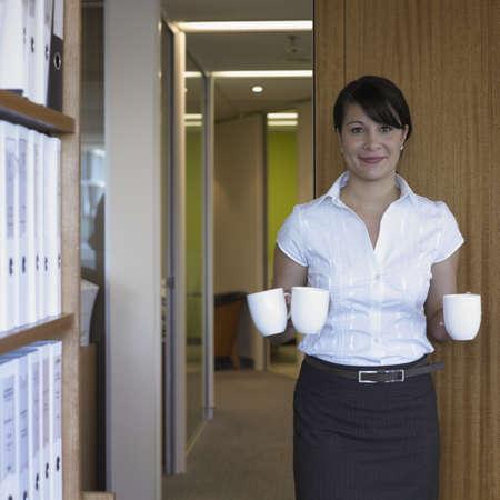 australian ethnicity: Hispanic businesswoman holding mugs