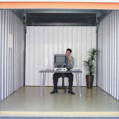 storage unit: Businessman working at desk in storage unit