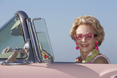 Senior woman driving pink convertible LANG_EVOIMAGES
