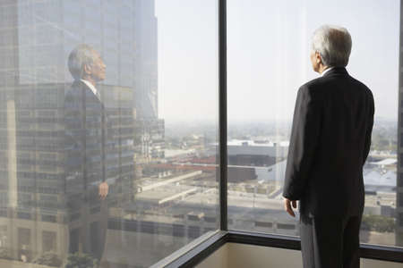 window view: Senior businessman looking out a window, Los Angeles, California, United States