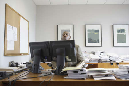 toiling: African businessman at his desk