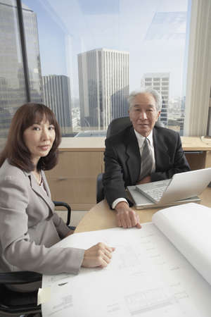 north western european descent: Senior Asian businessman and businesswoman looking at blueprints, Los Angeles, California, United States