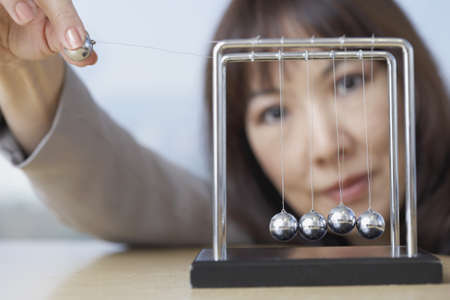 commencing: Close up of businesswoman starting perpetual motion device