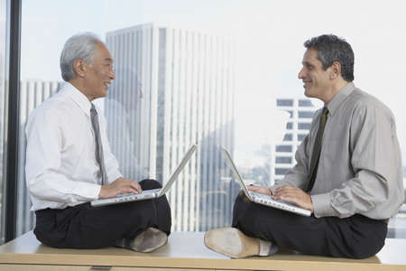 commencing: Two businessmen sitting cross-legged with laptops next to window, Los Angeles, California, United States