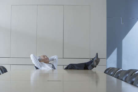 casualness: Senior Asian businessman sitting at head of conference table with his feet up