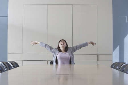 toiling: Businesswoman sitting at head of conference table stretching