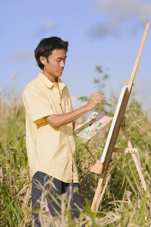 Asian man painting at easel outdoors, Florianopolis, Brazil