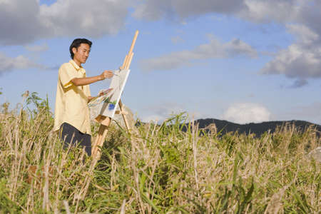 south american ethnicity: Asian man painting at easel outdoors, Florianopolis, Brazil