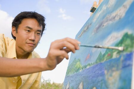 seriousness skill: Asian man painting at easel outdoors, Florianopolis, Brazil