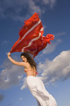 south american ethnicity: Young woman holding shawl over her head in the wind
