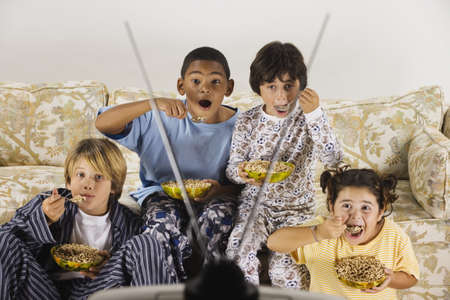 north western european descent: Group of children eating and watching television