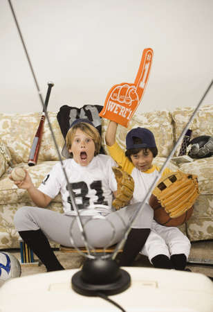 playing on divan: Two boys in sports gear watching television LANG_EVOIMAGES