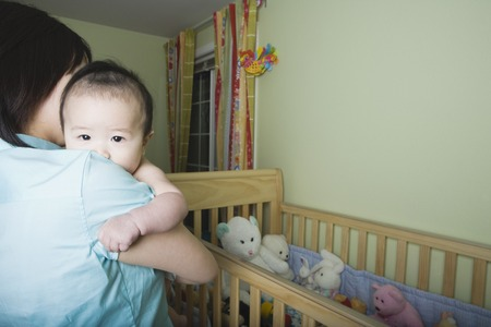 Mother holding Asian baby next to crib Banco de Imagens