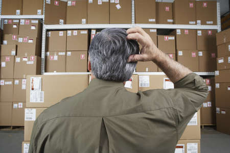 Businessman in warehouse scratching his head LANG_EVOIMAGES