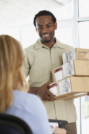 toiling: Woman signing for packages from African deliveryman