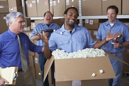 gaithersburg: Businessman with male warehouse workers joking around LANG_EVOIMAGES