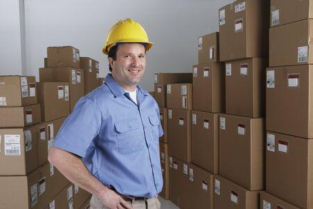 Male warehouse worker wearing hard hat in warehouse