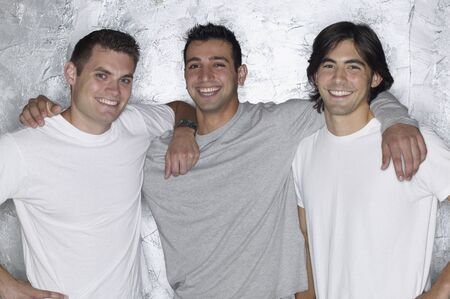 Three young men smiling and hugging