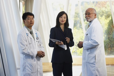 mid life: Two male doctors talking to Asian businesswoman, North Bethesda, Maryland, United States