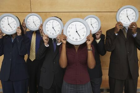 talker: Group of businesspeople holding clocks over their faces
