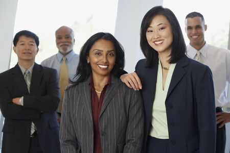 Two businesswoman with co-workers in the background