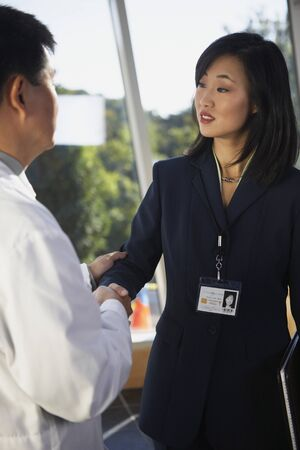 Asian businesswoman shaking hands with doctor, North Bethesda, Maryland, United States Stock Photo
