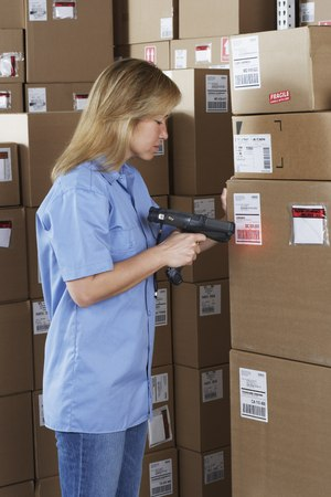 storing: Female warehouse worker scanning package