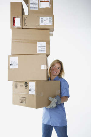 gaithersburg: Studio shot of female warehouse worker carrying packages LANG_EVOIMAGES