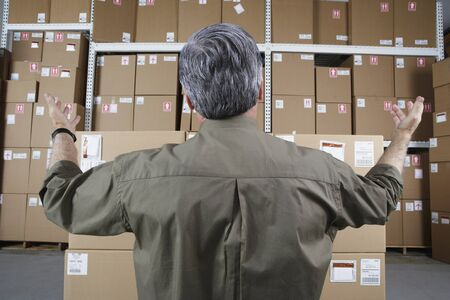gaithersburg: Businessman in warehouse looking at stacks of packages