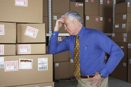 cardboard only: Businessman in warehouse with his head in his hand LANG_EVOIMAGES