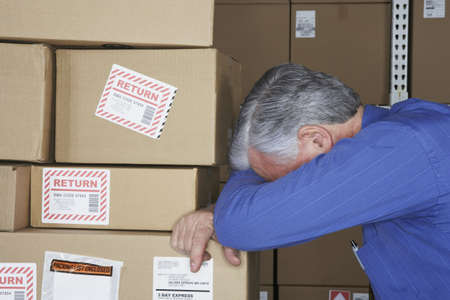 gaithersburg: Businessman in warehouse with head down on returned packages