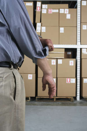 storing: Close up of businessman rolling up his sleeve in warehouse