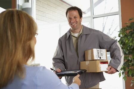 toiling: Woman signing for packages from deliveryman LANG_EVOIMAGES