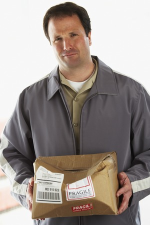 cardboard only: Man holding crushed package marked Fragile LANG_EVOIMAGES