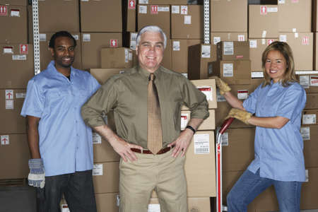gaithersburg: Businessman with warehouse workers in warehouse LANG_EVOIMAGES