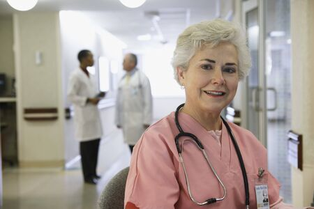 bethesda: Senior female nurse with doctors in background, Bethesda, Maryland, United States