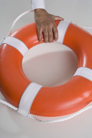 magistrate: Close up of mans hand holding life preserver LANG_EVOIMAGES