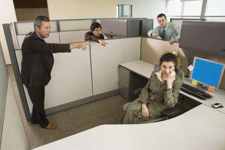 office cubicle: Businesspeople pointing at co-worker in office cubicle