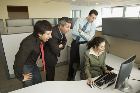 tugging: Businesspeople looking over co-workers shoulder at computer