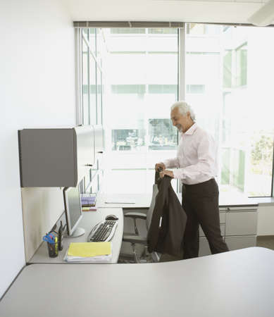 approaching: Middle-aged businessman hanging jacket on desk chair LANG_EVOIMAGES