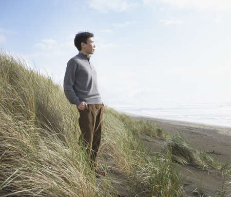 Asian man standing on the dunes, Ocean Beach, San Francisco, United States