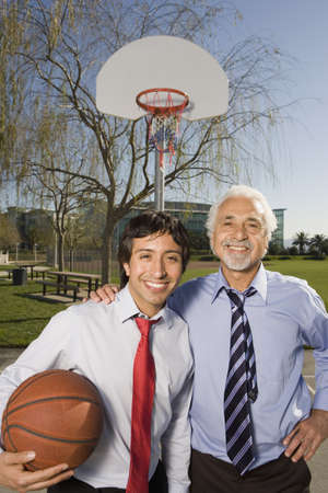 fathering: Two Hispanic businessmen on a basketball court, Redwood City, California, United States