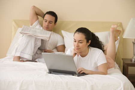 mate married: Hispanic couple lying on the bed reading and using a laptop